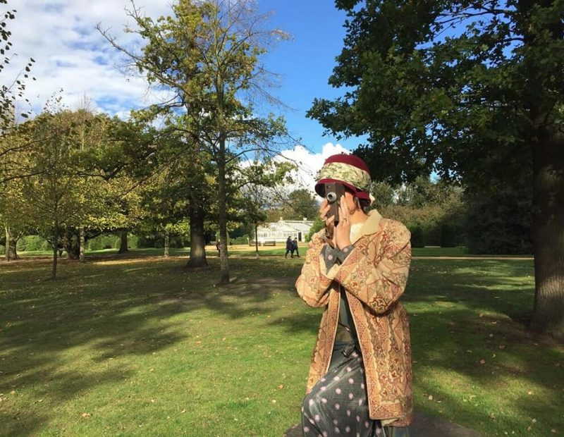 Hannah in Edwardian costume holding an old fashioned camera