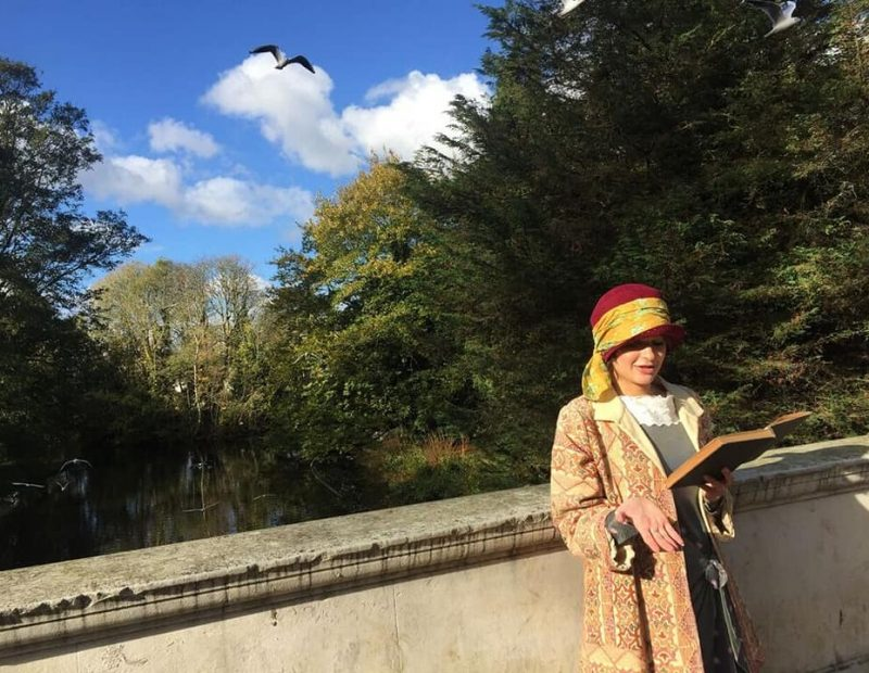 Hannah reads from a book on a sunny day while in period costume
