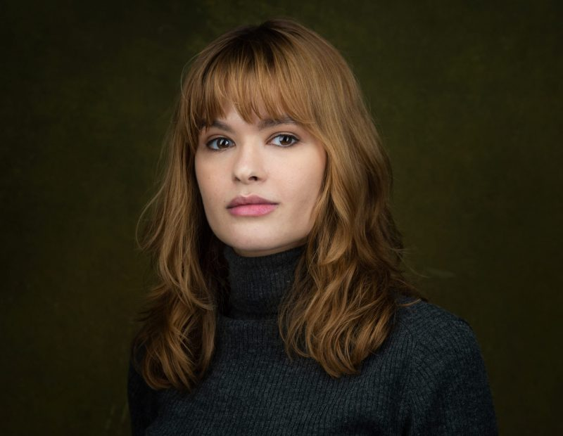Hannah's headshot. She has medium length brown wavy hair with a fringe. She has brown eyes and is looking at the camera